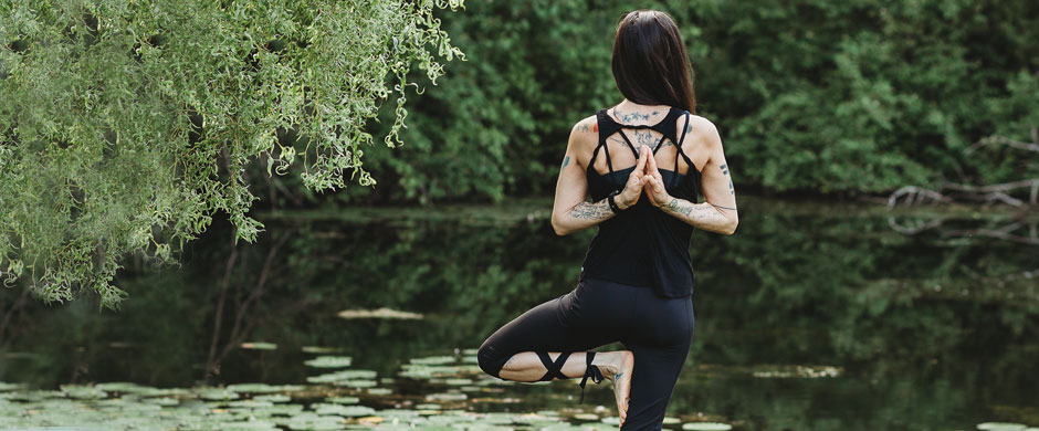 Woman doing yoga in front of a pond