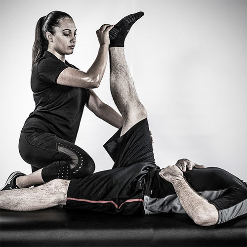 Woman Stretching Man's Leg at Stretch U